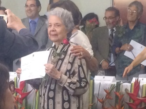 A woman honored by the Amnesty Commission poses with her certificate and red rose